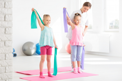 two smiling little girls having a physical therapy session